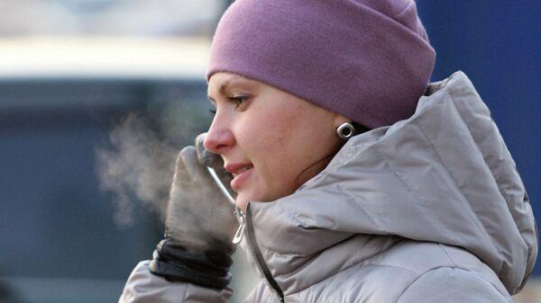 Девушка говорит по телефону в мороз. Архив