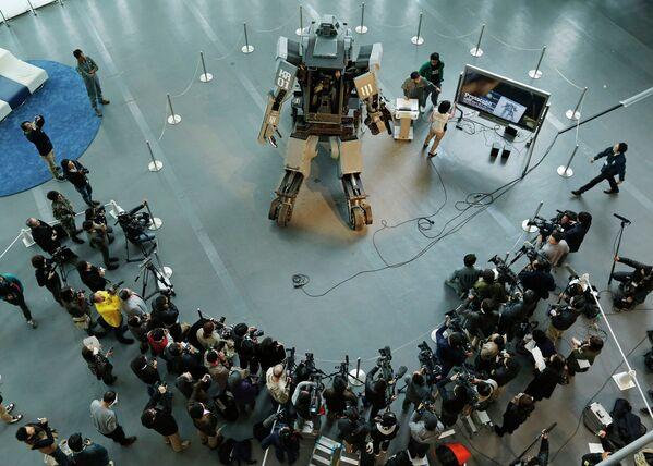 Представители СМИ у боевого робота Kuratas на выставке в Токио, Япония
