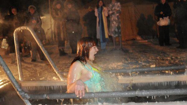 Женщина купается в проруби в праздник Крещения Господня, архивное фото