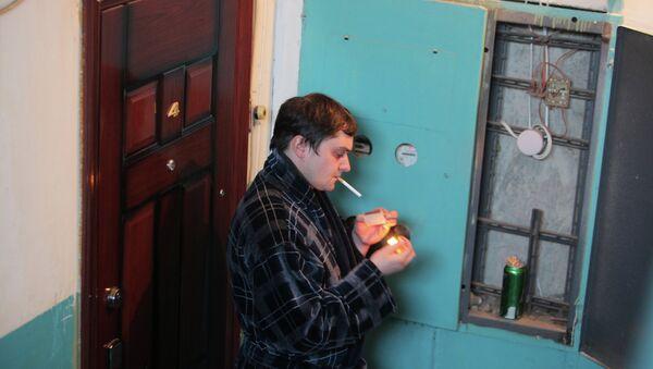 Мужчина курит в подъезде жилого дома, архивное фото