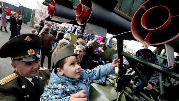 Офицер с внуком у боевой машины БМ-32 после военного парада