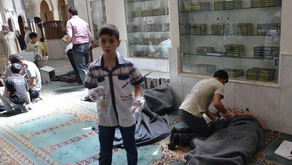Люди помогают постадавшим от газовой атаки в мечети в окрестностях Дамаска