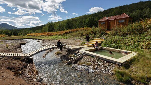 Туристы купаются в Таловских термальных источниках в природном парке Вулканы Камчатки