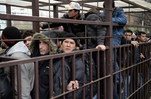 Граждане иностранных государств стоят в очереди в центральное отделение УФМС РФ по Москве