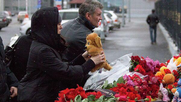 Алые гвоздики несут горожане к месту трагедии в Казани