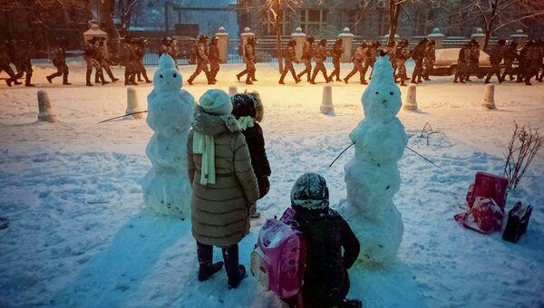 Дети набрюдают за сотрудниками правоохранительных органов в Киеве