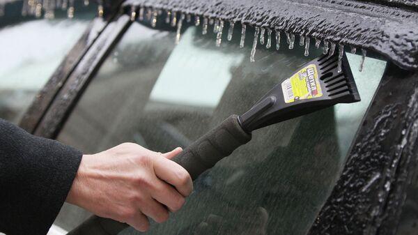 Мужчина счищает наледь со стекла автомобиля