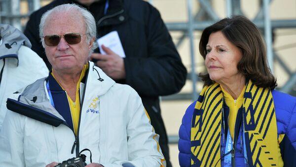 Король Швеции Карл XVI Густав и его супруга королева Швеции Сильвия во время индивидуальной гонки в соревнованиях по лыжным гонкам среди мужчин