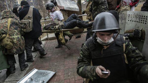 Сторонники оппозиции несут раненного во время столкновений с сотрудниками правопорядка в Киеве