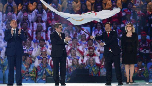 Президент Международного олимпийского комитета Томас Бах (второй слева) передает Олимпийский флаг мэру города Пхенчхана Ли Сок Рэ