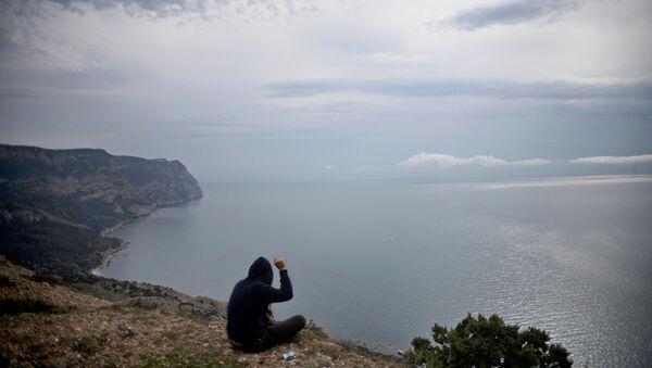 Молодой человек на скалистом побережье Черного моря. Архивное фото