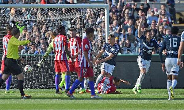 Защитник Мельбурна Ник Анселл (второй справа) празднует забитый гол в матче с Атлетико