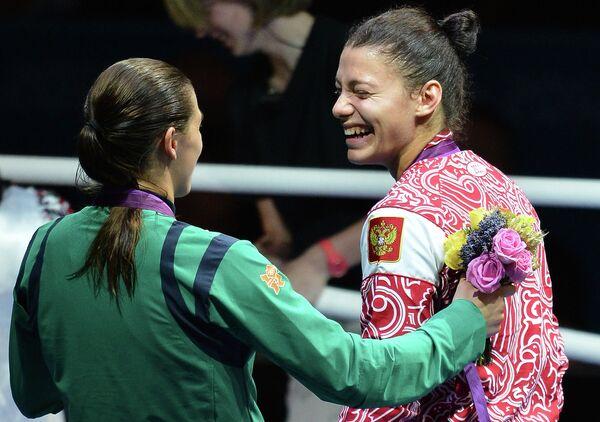 Ирландка Кэти Тэйлор, завоевавшая золотую медаль, и россиянка Софья Очигава, завоевавшая серебряную медаль, (слева направо) во время церемонии награждения на ХХХ летних Олимпийских играх в Лондоне