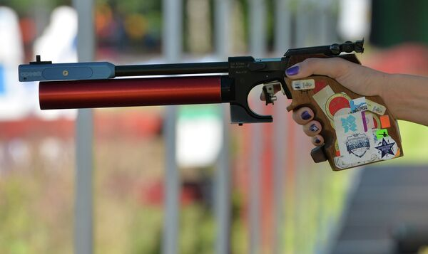 Пневматический пистолет в руке спортсменки на тренировке