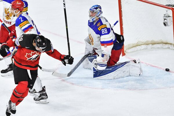 Форвард сборной Канады Натан Маккиннон (слева) радуется заброшенной шайбе в ворота Андрея Василевского