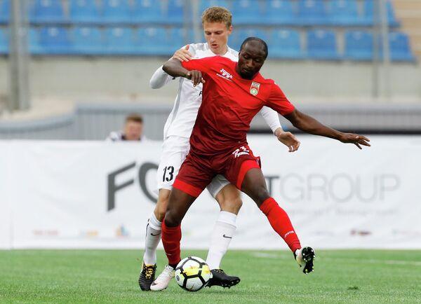 Защитник Тосно (слева) Виталий Шахов и нападающий Уфы Кеинде Фатай