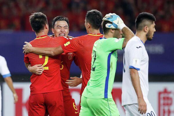 Футболисты сборной Китая радуются забитому мячу в ворота команды Узбекистана