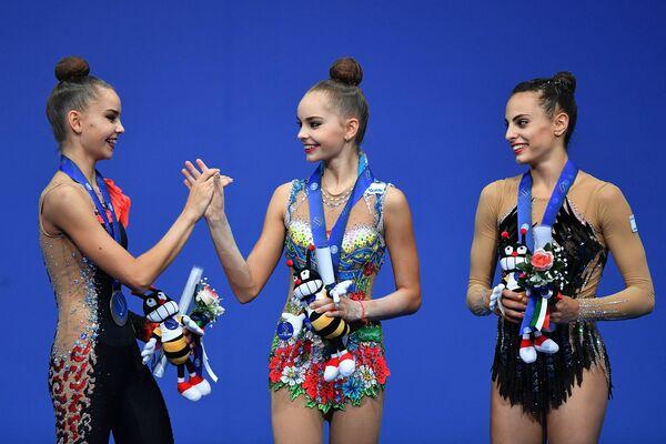 Призеры индивидуальных соревнований в упражнениях с лентой на чемпионате мира по художественной гимнастике в итальянском Пезаро во время церемонии награждения (слева направо): Дина Аверина (Россия)- серебряная медаль, Арина Аверина (Россия) - золотая медаль, Линой Ашрам (Израиль) - бронзовая медаль