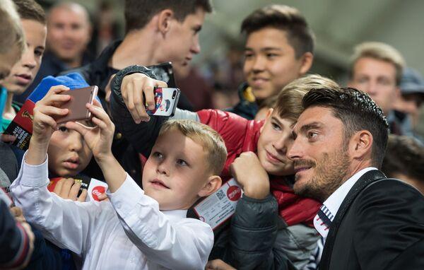 Бывший футболист сборной Испании Альберт Риера фотографируется с юными омичами