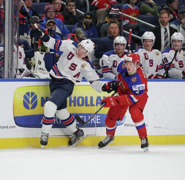 Защитник молодежной сборной России по хоккею Александр Шепелев и нападающий молодежной сборной США по хоккею Брэди Ткачак (справа налево на первом плане)