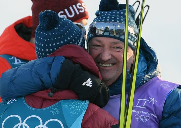 Тренер российских лыжников Маркус Крамер поздравляет российского спортсмена Дениса Спицова
