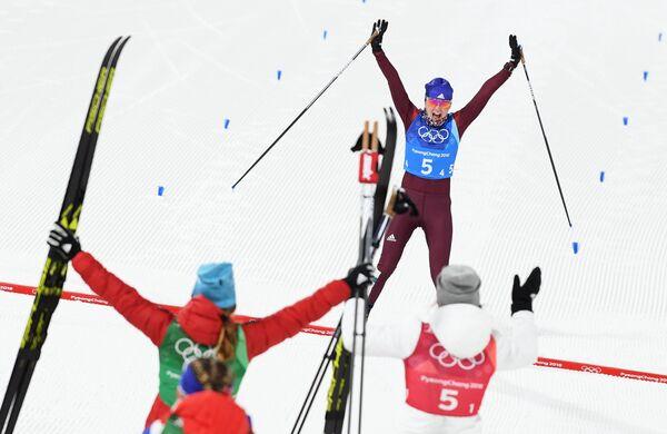 Российская лыжница Анна Нечаевская финиширует в олимпийской эстафете