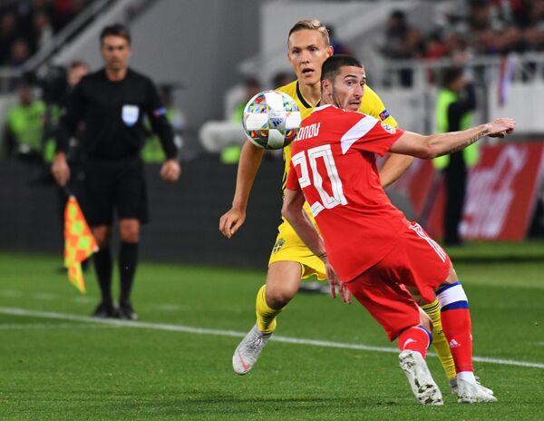 Защитник сборной Швеции Людвиг Аугустинсон и полузащитник сборной России Алексей Ионов (справа)