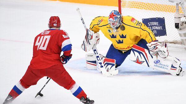 Форвард сборной России Евгений Кетов (слева) забрасывает шайбу в ворота Магнуса Хелльберга