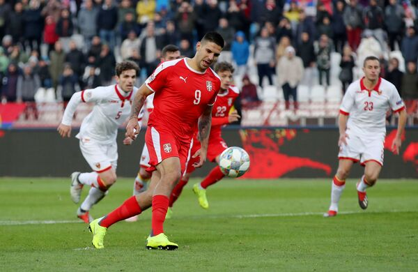 Форвард сборной Сербии Александар Митрович забивает мяч в ворота черногорцев