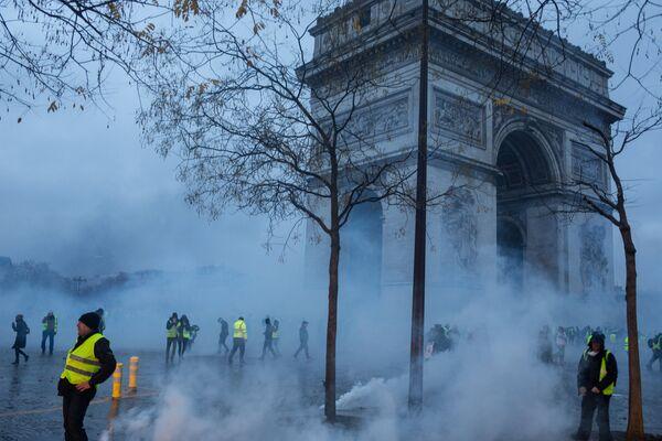 Участники протестной акции движения автомобилистов желтые жилеты, выступавшего с требованием снижения налогов на топливо, в районе Триумфальной арки в Париже