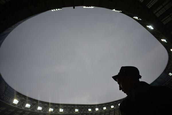 Сотрудник полиции следит за безопасностью на стадионе Лужники во время сильного дождя