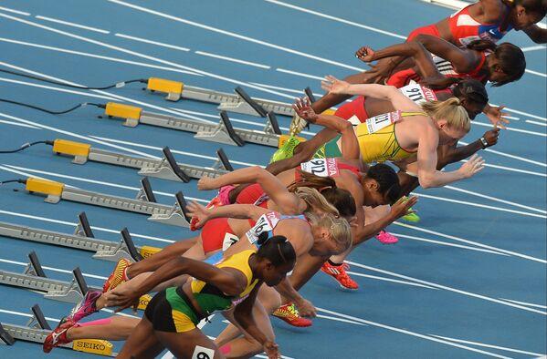 Старт забега на 100 метров с барьерами среди женщин