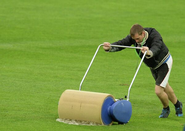 Работник стадиона убирает воду с футбольного поля перед матчем отборочного тура Чемпионата мира-2014 между сборными командами России и Люксембурга