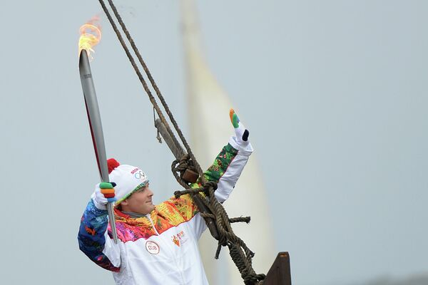 Факелоносец плывет на ладье по Оке во время эстафеты Олимпийского огня в городе Муром