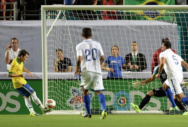 Нападающий сборной Бразилии Бернард забивает мяч в ворота сборной Гондураса