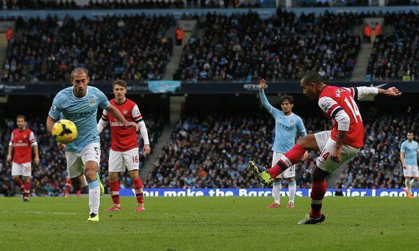 Нападающий Арсенала Тео Уолкотт забивает мяч в ворота Манчестер Сити