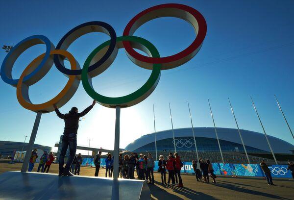 Мужчина фотографируется с олимпийскими кольцами в Олимпийском парке в Сочи