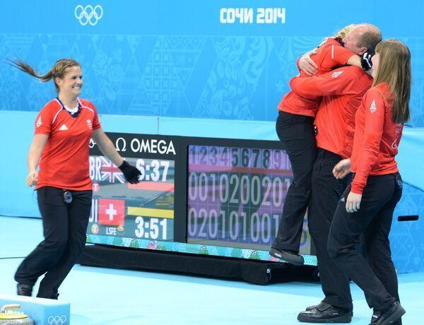 Слева направо: Вики Адамс (Великобритания), Анна Слоун (Великобритания) и тренер Дэвид Хэй (Великобритания) радуются победе в матче за третье место между сборными командами Великобритании и Швейцарии в соревнованиях по керлингу среди женщин на XXII зимних Олимпийских играх в Сочи.