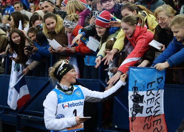 Мари Дорен-Абер (Франция) раздает автографы после окончания эстафетной гонки в соревнованиях среди смешанных команд на Гонке чемпионов 2014