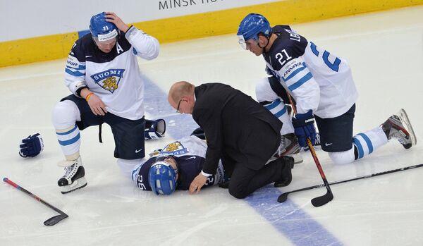 Врач оказывает первую помощь игроку сборной Финляндии Пекке Йормакку (в центре)