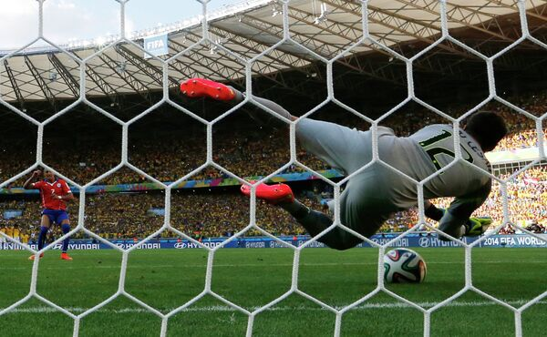 Голкипер сборной Бразилии Жулио Сезар отбивает удар нападающего сборной Чили Алексиса Санчеса