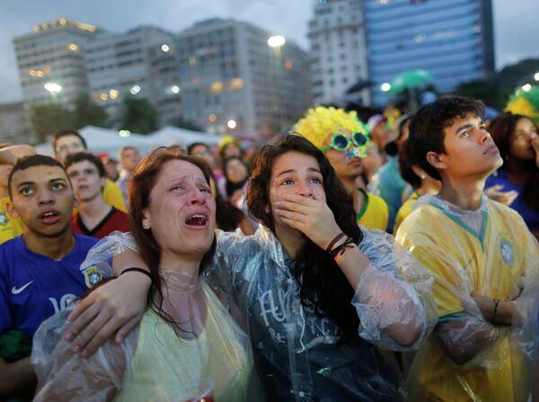 Болельщики сборной Бразилии плачут, наблюдая за игрой своей команды.