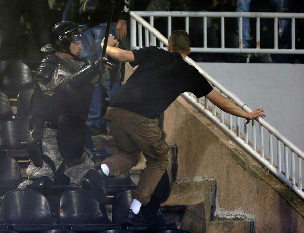 Полицейский и фанат на матче Партизан - Црвена Звезда