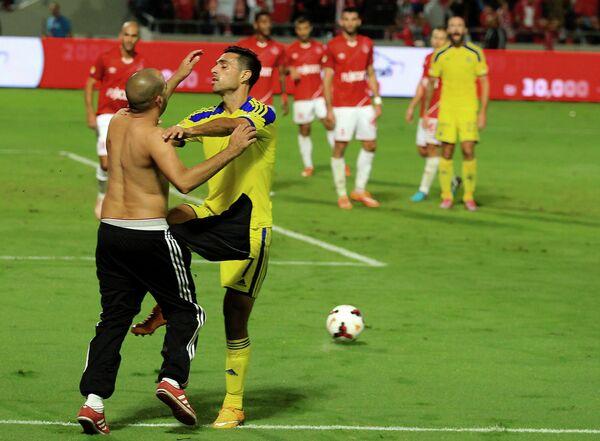 Один из болельщиков прорвался на поле и напал полузащитника Маккаби Эрана Захави (справа)