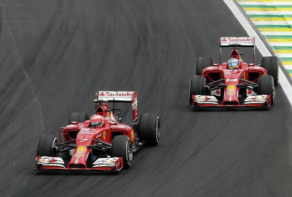 Пилоты Феррари Кими Райкконен и Фернандо Алонсо (справа) на дистанции Гран-при Бразилии