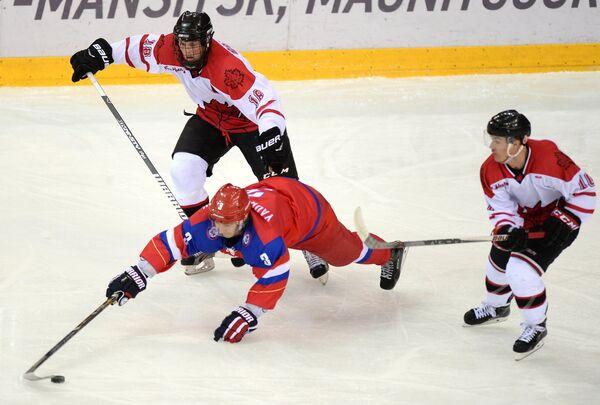 Защитник сборной России Дмирий Ядришников (в центре) и игроки сборной Канады Крис Гербек, Раян Храмченко (слева направо)