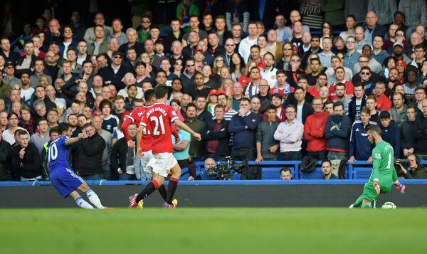 Полузащитник Челси Эден Азар забивает мяч в ворота голкипера Манчестер Юнайтед Давида Де Хеа (справа)