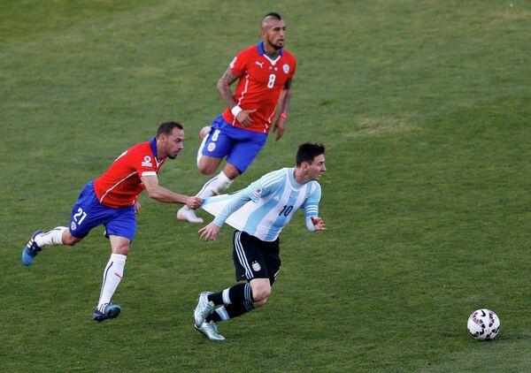 Полузащитник сборной Чили Марсело Диас (слева) придерживает за футболку форварда сборной Аргентины Лионеля Месси