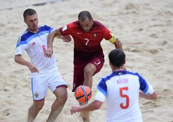 Игроки сборной России по пляжному футболу Илья Леонов (слева) и Юрий Крашенниников (справа) и игрок сборной Португалии Маджер (в центре)