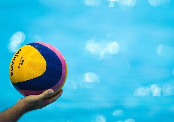Судья держит мяч во время матча по водному поло